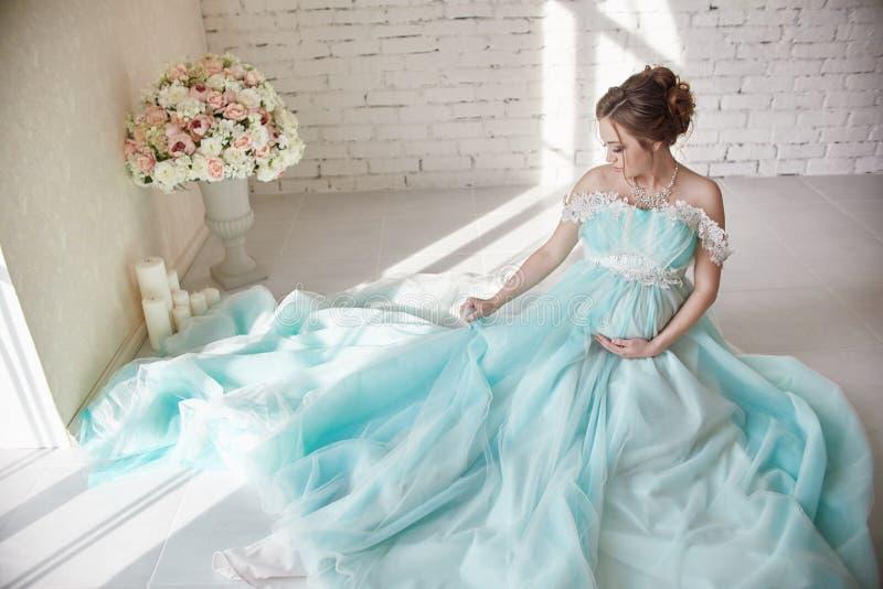 Schwangerschaft, Frau, die auf dem Boden in einem deluxen Kleid sitzen und Griff lizenzfreie stockfotos