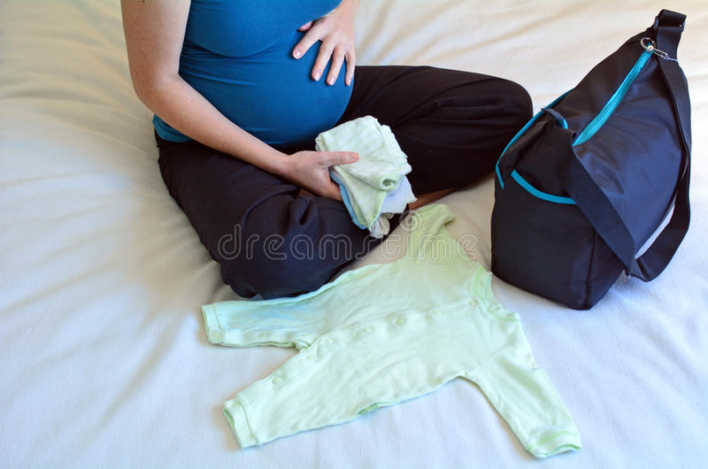 Schwangerschaft - schwangere Frau, die eine Krankenhaus-Tasche verpackt stockfotos