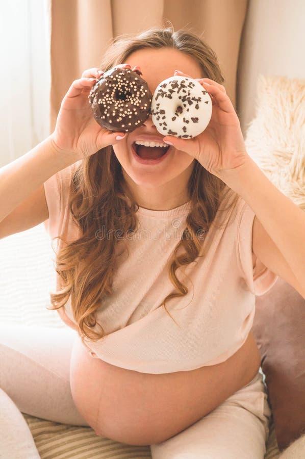 Schwangerschaft und Nahrung Schwangere Frau, die Schaumgummiringe und Tee im Bett, freier Raum genie?t Konzept der Erwartung und  stockfoto