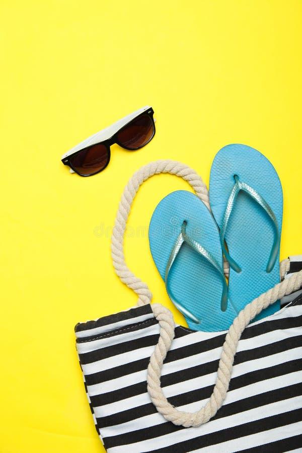 Schwarz-weiße gestreifte Strandtasche mit blauen Gummiflipflops und Sonnenbrille lizenzfreies stockfoto