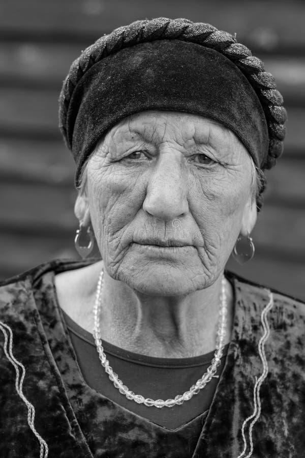 Schwarz-weißes Porträt der Nahaufnahme einer älteren Frau des Dorfs in einem nationalen Kostüm lizenzfreies stockfoto