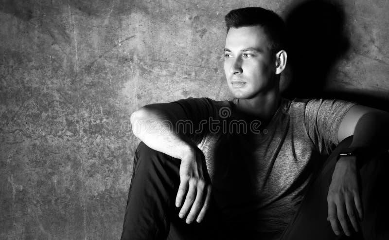 Schwarz-weißes Porträt des athletischen Mannes im T-Shirt und in sweatpants, die durch die Betonmauer sitzen und der Blicke am Ra stockbilder