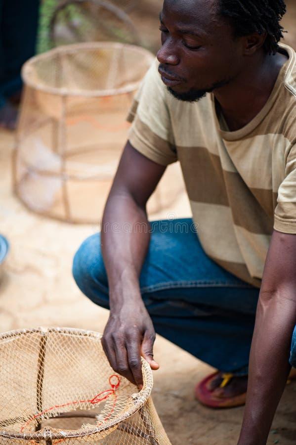 Schwarzafrikanerleute, die Fische erfassen und vorbereiten lizenzfreie stockfotografie