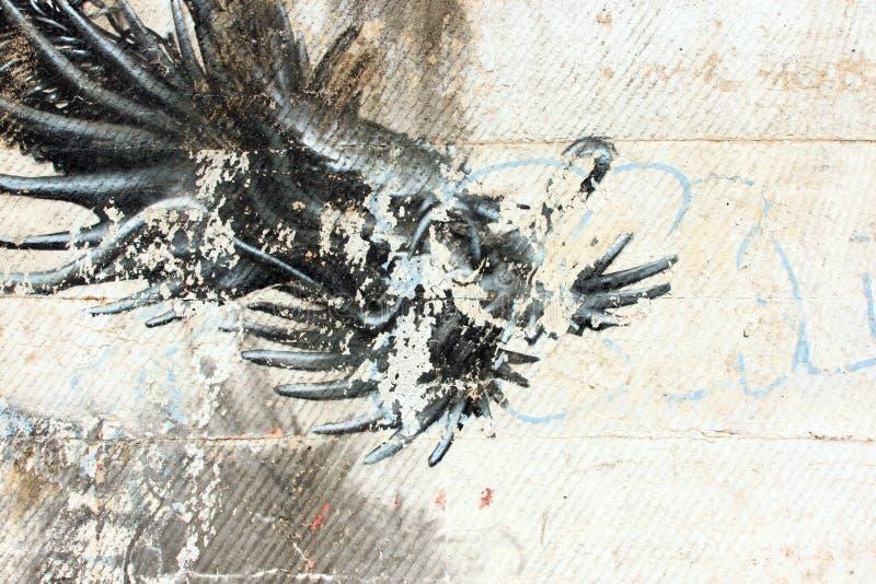 Schwarze, abstrakte Graffiti auf einer schmutzigen weißen Wand lizenzfreie stockfotos