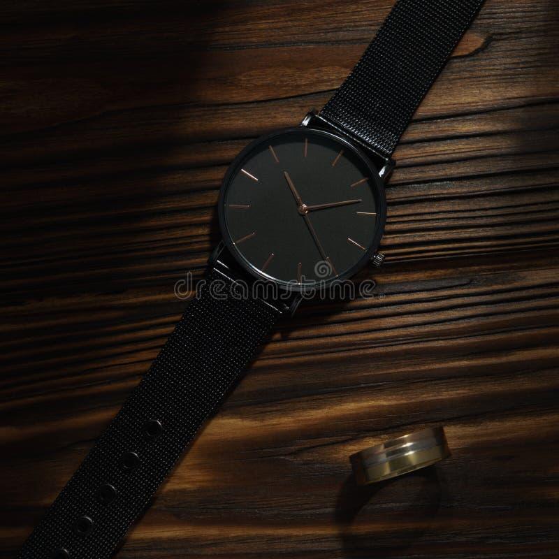 Schwarze Armbanduhr und goldener Ring auf hölzernem Hintergrund stockbilder