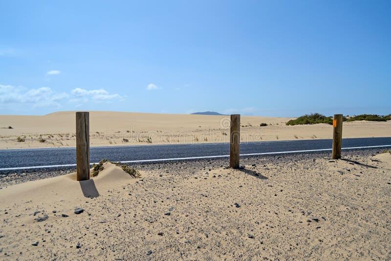 Schwarze Asphaltstraße unter Wüstendünen, Corralejo, Fuerteventura, lizenzfreie stockbilder