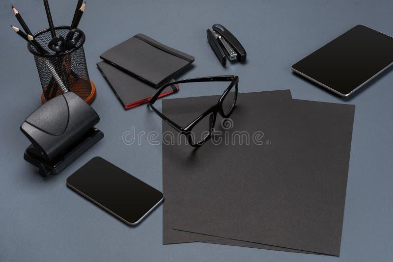 Schwarze Büromaterialsammlungs-Ebenenlage Draufsicht über Satz Briefpapier mit Smartphone und Tablette stockfoto