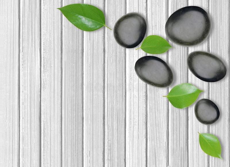 Schwarze Badekurortsteine und Grünblätter auf hölzernem stockbilder