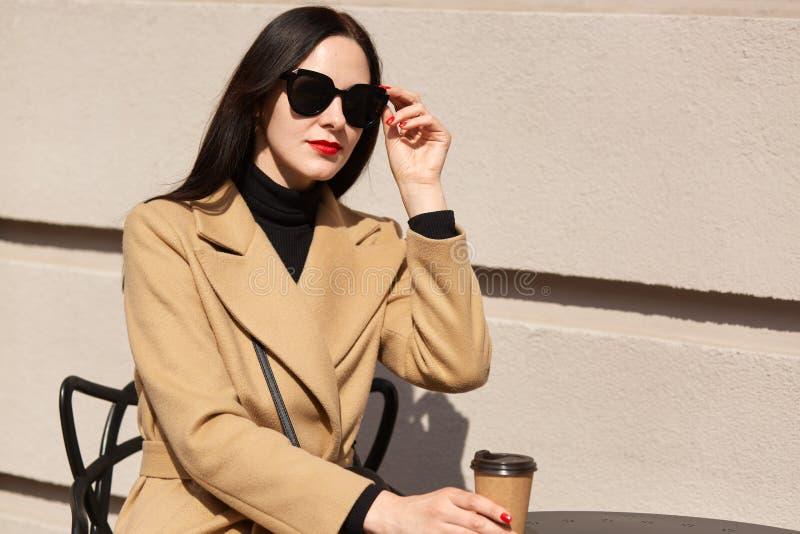 Schwarze behaarte europäische magnetische Frau, die braunes papercup in einer Hand, die schwarze Sonnenbrille berührend hält u stockfoto