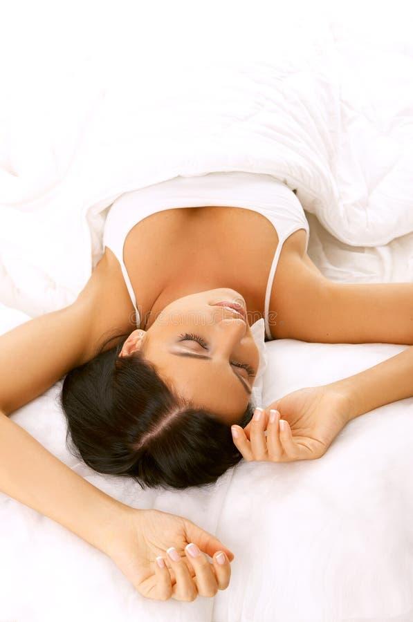 Schwarze behaarte Schönheit im Bett stockfotografie