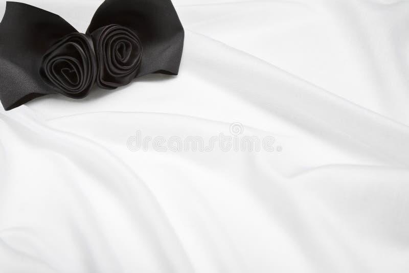 Schwarze Blumen auf weißem Satin stockbild