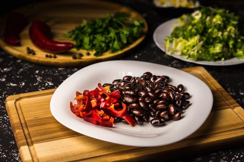 Schwarze Bohnen mit Gemüsepaprikas auf einer weißen Platte und einem hölzernen Brett stockfotografie