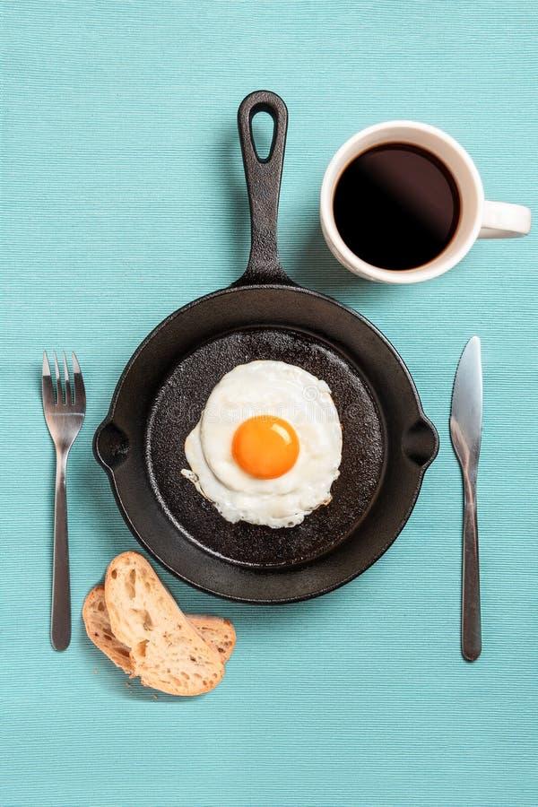 Schwarze Bratpfanne mit durcheinandergemischten Eiern, Gabel, Messer, mit Tasse Kaffee zwei Stücke Brot auf einer Türkistischdeck lizenzfreie stockfotos