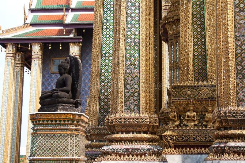 Schwarze Buddha-Statue und Spaltenrasterdetail stockfotografie