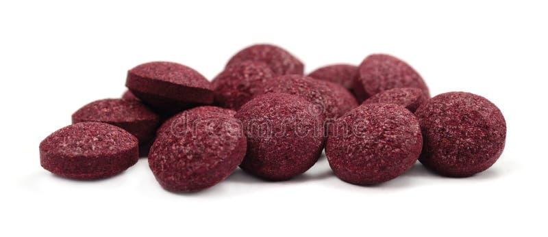 Schwarze Chokeberryfruchtpillen, große ausführliche lokalisierte Tablettenmakronahaufnahme, organischer roher aronia melanocarpa  stockbild