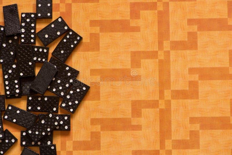Schwarze Dominos auf einem orange Hintergrund stockfotos