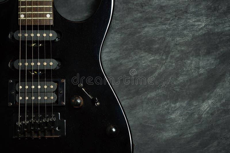 Schwarze E-Gitarre auf schwarzem Zementboden lizenzfreie stockfotos