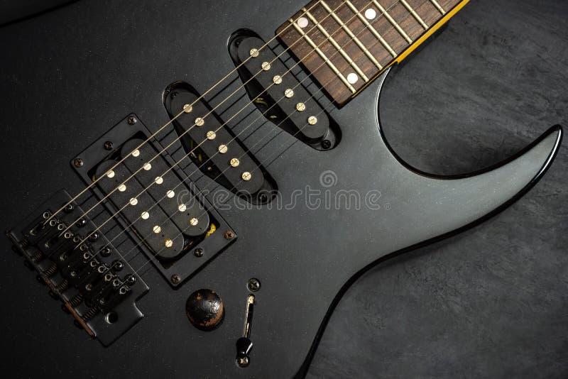 Schwarze E-Gitarre auf schwarzem Zementboden lizenzfreies stockfoto