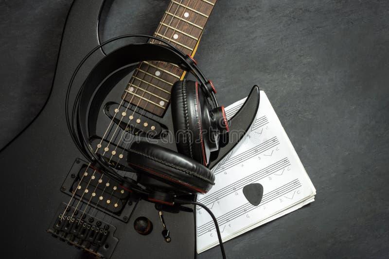 Schwarze E-Gitarre und Kopfhörer auf schwarzem Zementboden lizenzfreie stockfotografie