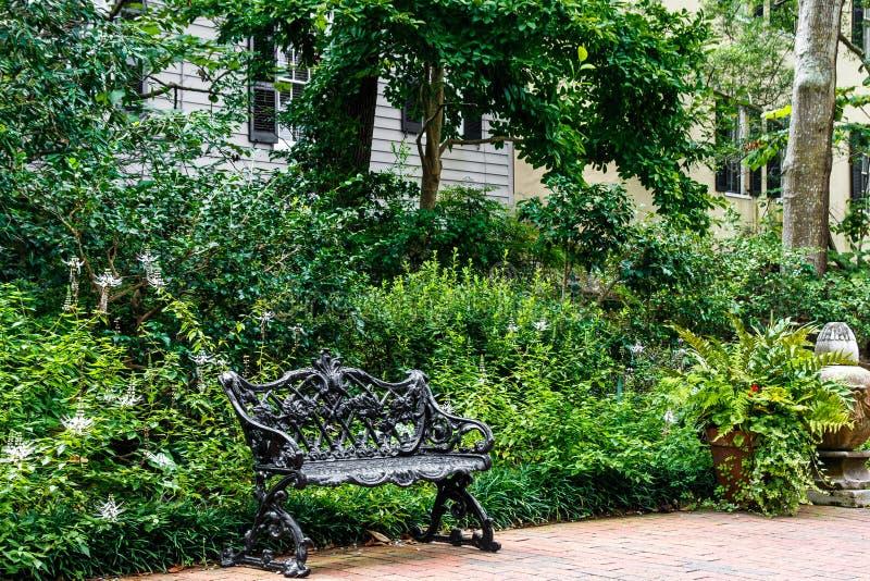 Schwarze Eisen-Bank im Garten stockbilder