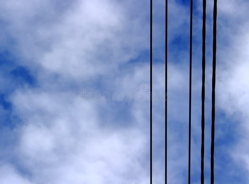 Schwarze elektrische Drähte auf einem Hintergrund eines bewölkten blauen Himmels lizenzfreie stockfotos