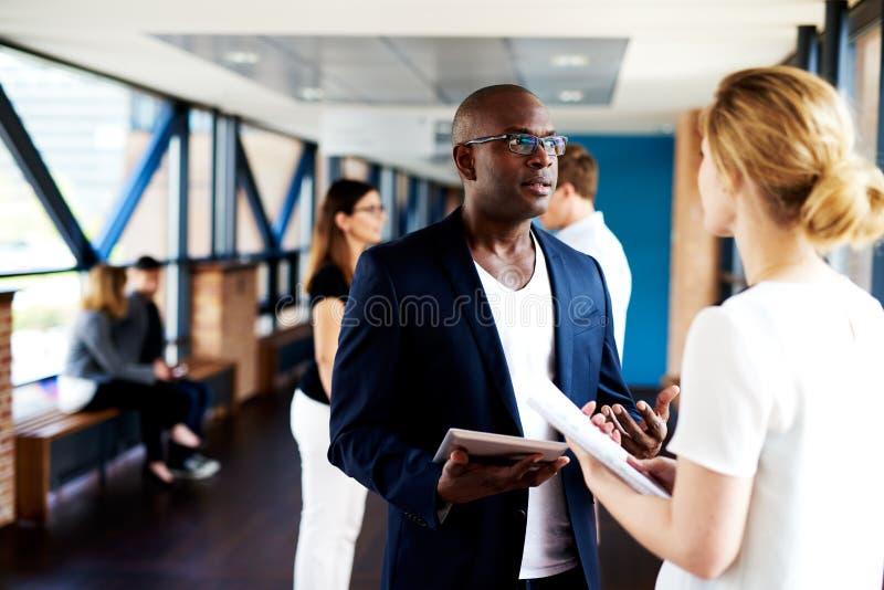 Schwarze Exekutivunterhaltung mit weißem weiblichem Kollegen stockfotos
