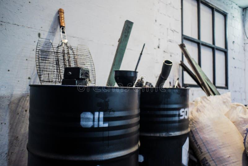 Schwarze Fässer des alten Öls auf weißem Schmutzziegelstein stockbilder