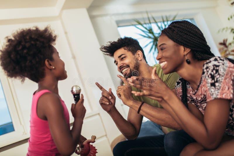 Schwarze Familie genießen, Karaoke zu singen stockbild