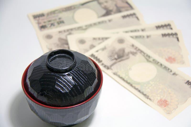 Schwarze Farbrote Rand Misosuppenschüssel mit Yenbanknoten von Japan auf dem weißen Hintergrund lizenzfreie stockfotografie