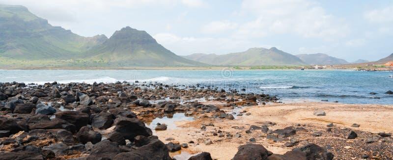 Schwarze Felsensteinsand-Strandküste vor Blau lizenzfreie stockfotos
