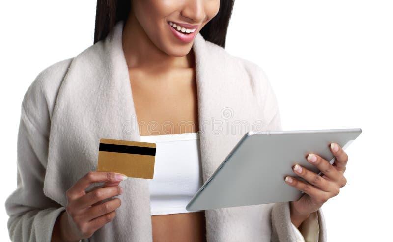 Schwarze Frau des Mulatten, die digitalen Tablet-Computer und Lohn von der Goldkreditkarte hält Weiche Farben Auf Weiß stockfoto