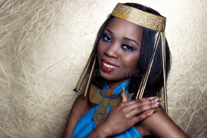 Schwarze Frau des schönen dunkelhäutigen Mädchens im Bild der ägyptischen Königin mit rote Lippenhellem Make-up demonstriert lang lizenzfreies stockbild