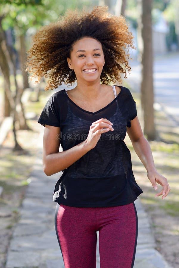 Schwarze Frau, die in einen städtischen Park läuft stockfotos