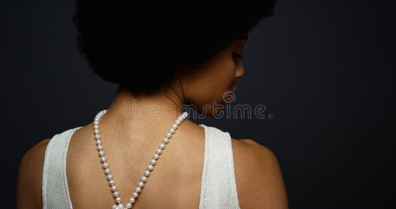 Schwarze Frau, die elegante Perlenhalskette trägt stockbild