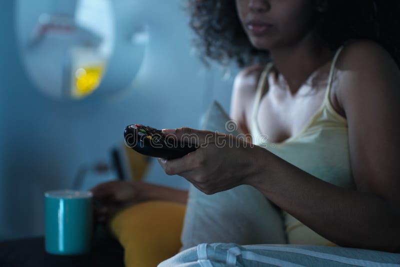 Schwarze Frau, die Fernsehkanal mit Direktübertragung nachts ändert lizenzfreie stockfotos