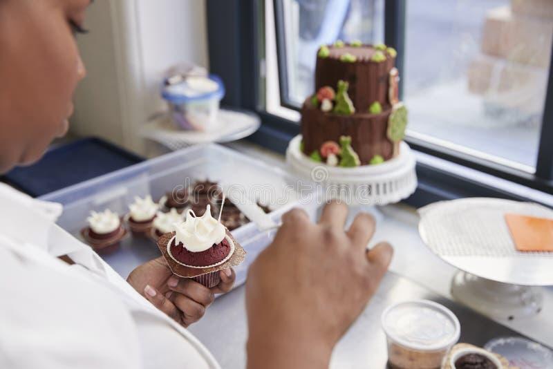 Schwarze Frau, die Lebensmittel in einer Bäckerei, über Schulteransicht zubereitet stockfoto