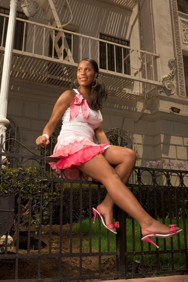 Schwarze Frau im rosafarbenen Rock, der auf geschmiedetem Zaun sitzt stockbild