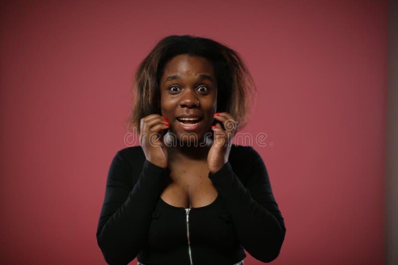 Schwarze Frau mit tiefer Spaltung in angenehmer Überraschung lizenzfreies stockbild