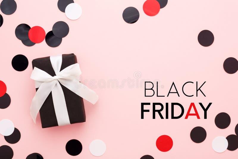 Schwarze Freitag-Karte mit Geschenkbox und Konfettis auf rosa Hintergrund lizenzfreie stockfotografie