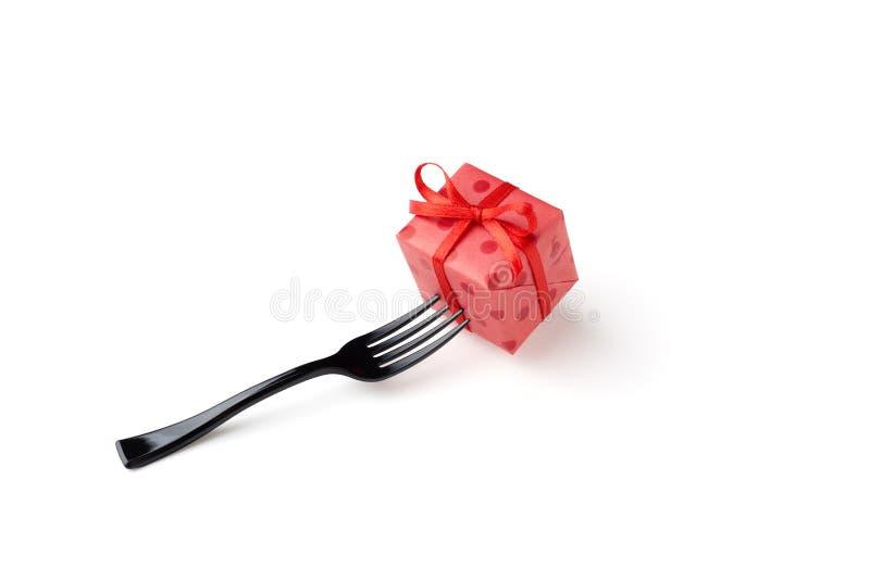 Schwarze Gabel und rote Geschenkbox lokalisiert an weißem Hintergrund Feiertag stockbild