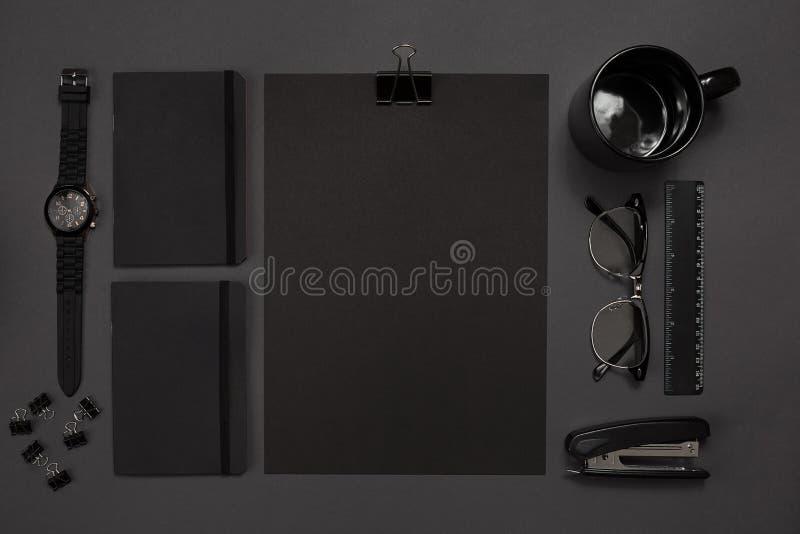 Schwarze Gegenstände vom Büro auf einem dunkelgrauen Hintergrund Arbeit und Kreativität Beschneidungspfad eingeschlossen stockbild