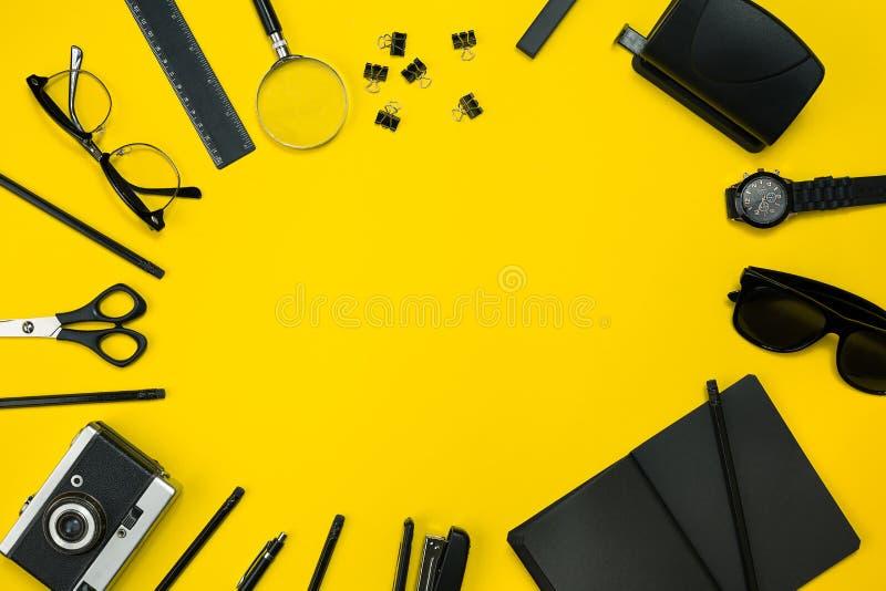 Schwarze Gegenstände vom Büro auf einem gelben Hintergrund Arbeit und Kreativität Beschneidungspfad eingeschlossen stockfotos