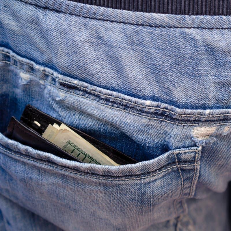Schwarze Geldbörse mit dem Geld, haftend aus der Gesäßtasche von Th heraus lizenzfreies stockbild