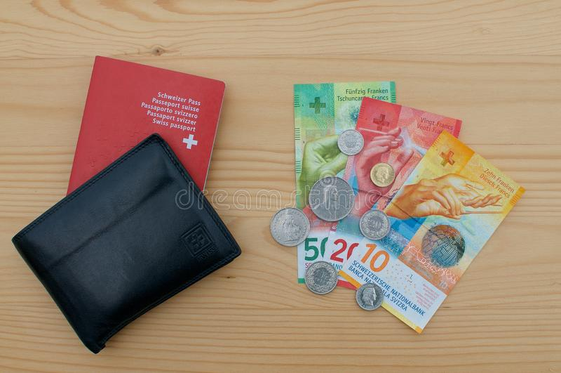 Schwarze Geldbörse mit Schweizer Pass und Schweizer Währung stockbild