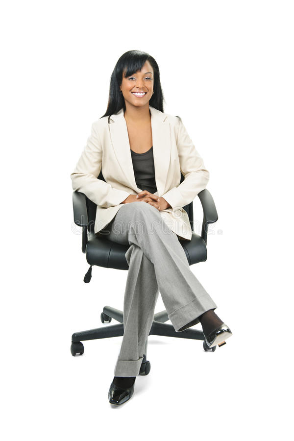 Schwarze Geschäftsfrau, die im Bürostuhl sitzt lizenzfreies stockbild