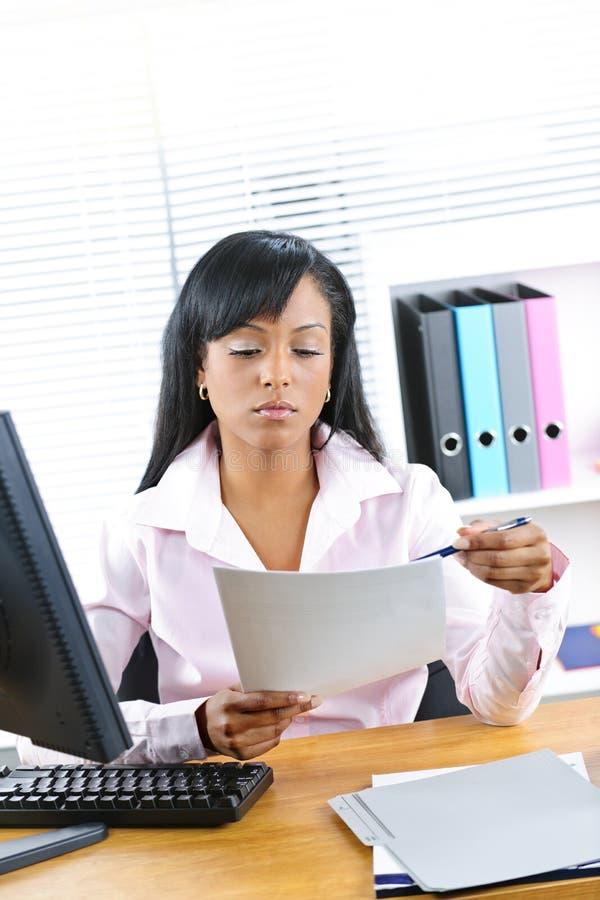 Schwarze Geschäftsfrau, die am Schreibtisch arbeitet lizenzfreies stockfoto