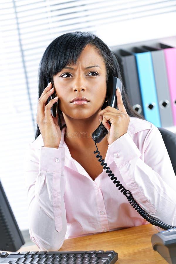 Schwarze Geschäftsfrau, die zwei Telefone am Schreibtisch verwendet lizenzfreie stockfotos