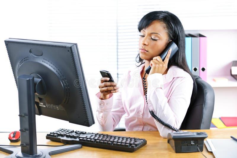 Schwarze Geschäftsfrau, die zwei Telefone am Schreibtisch verwendet lizenzfreies stockfoto
