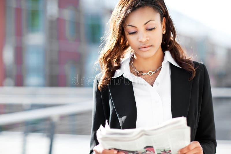 Schwarze Geschäftsfraulesezeitung lizenzfreie stockfotografie