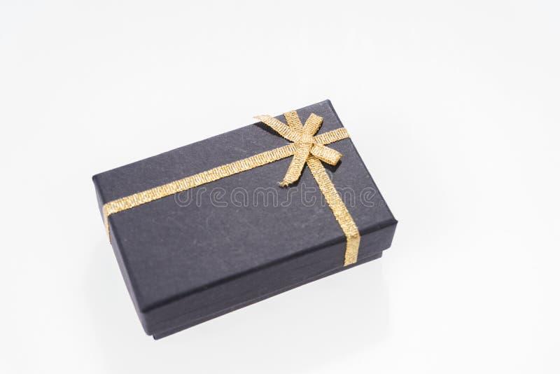 Schwarze Geschenkbox mit dem Goldband lokalisiert stockbild